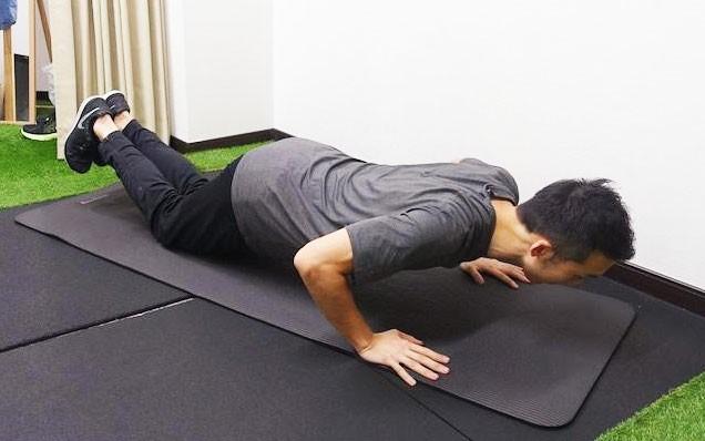 背筋を伸ばしたまま肘を曲げていく。胸がつく寸前まで体を沈めていこう。