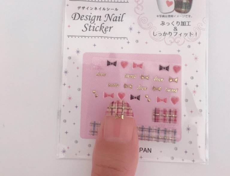 4、ライトベージュを塗った上に、ピンク系のチェック柄ネイルシールを爪の形に切って貼ります。さらに、真ん中にリボンシールを貼ります。